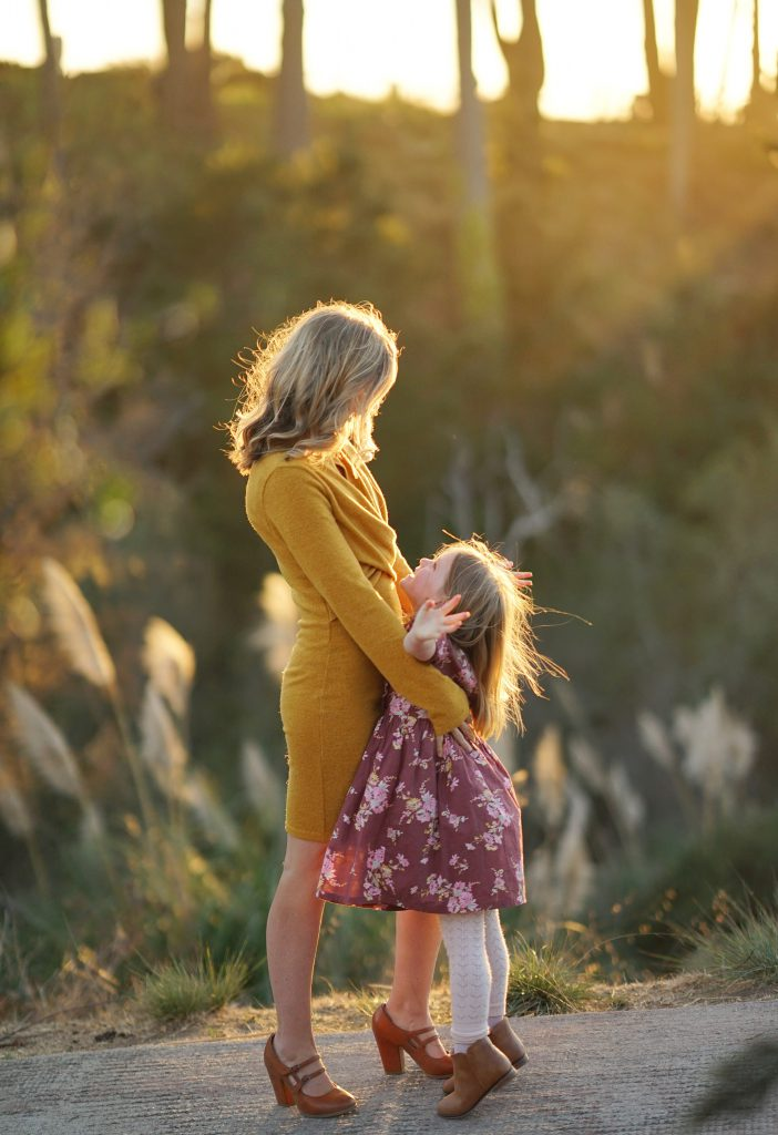 Mom and daughter share an embrace with the sun setting behind them
